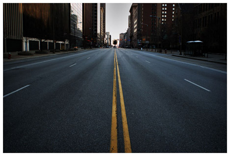empty-city-street-painted-double-yellow-line-perspective-asphault-buildings-tree-at-end-of-road-photo